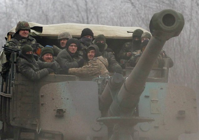 Ukrainian government soldiers ride on a vehicle on the road between the towns of Dabeltseve and Artemivsk, Ukraine, Saturday, Feb. 14, 2015