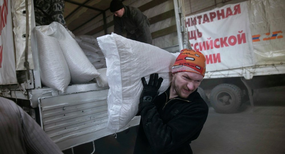 A man carries a sack of flour from a truck, that is part of a Russian humanitarian convoy delivering food, in Donetsk, February 15, 2015