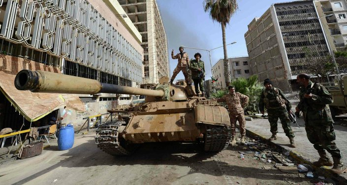 Members of the Libyan pro-government forces, backed by locals, gather on a tank outside the Central Bank, near Benghazi port, January 21, 2015