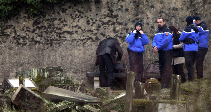 Police officers investigate the site of defaced tombstones at the Jewish cemetery of Sarre-Union, eastern France, Monday, Feb. 16, 2015
