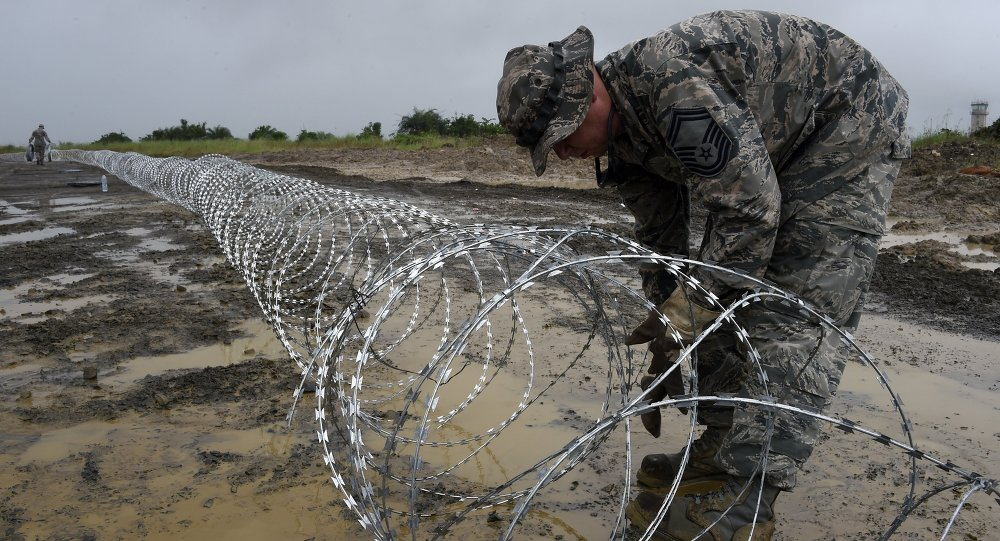 An US air Force soldier delimits with barbed wire the position of the next Ebola treatment center reserved for contaminated healthcare workers