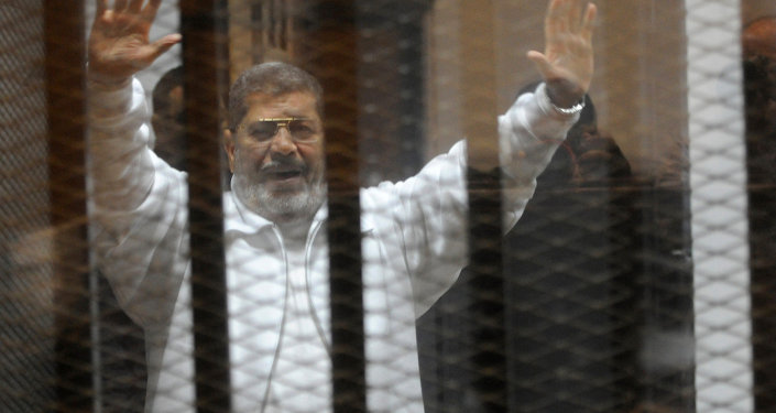 Egypt's deposed Islamist president Mohamed Morsi waves from inside the defendant's cage during his trial at the police academy in Cairo.