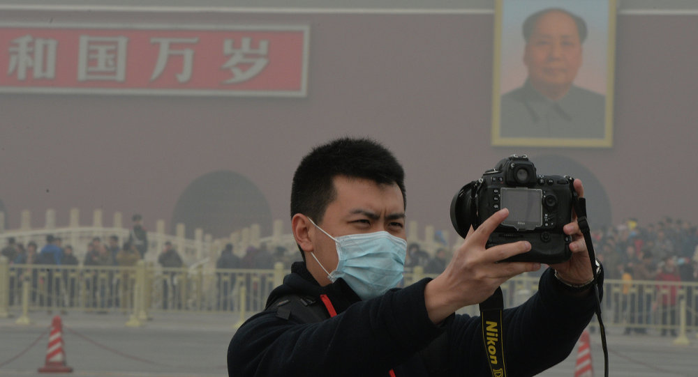 A Chinese tourist takes a photo while wearing a face mask in Tiananmen Square as heavy air pollution continues to shroud Beijing on February 26, 2014
