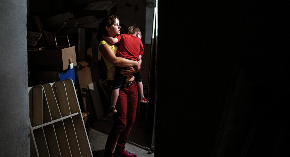 A woman holds her child in her arms as they are hidding in a bomb shelter in an orphanage during a shelling in the town of Makiyivka on August 19, 2014