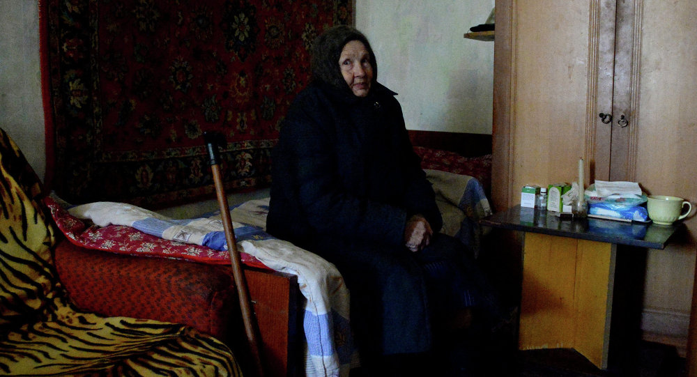 An old resident of Donetsk in an apartment of the house damaged in shelling.