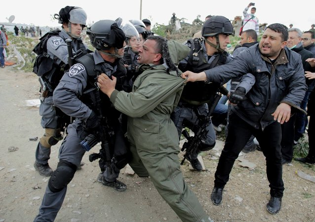 A Palestinian man scuffles with Israeli border policemen as they clear a protest on land that Palestinians said was confiscated by Israel for Jewish settlements, near the West Bank town of Abu Dis near Jerusalem