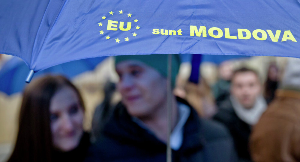 Moldovan students hold an umbrella that uses the European Union symbol to form the sentence I am Moldova