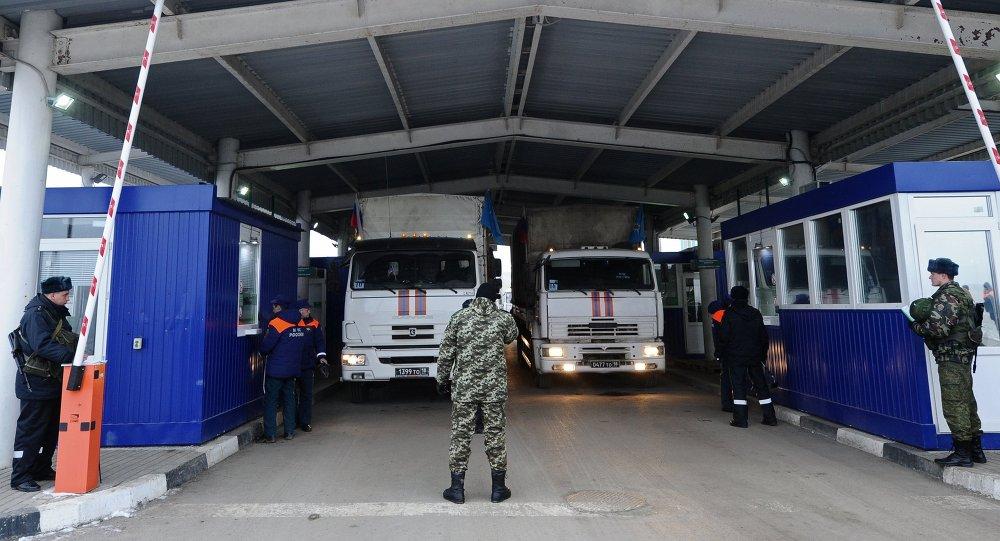 A Ukrainian customs officer near trucks carrying Russian humanitarian aid for Donbass residents, at the Matveyev Kurgan checkpoint