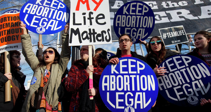 Abortion rights advocates hold signs while anti-abortion demonstrators walk by during the annual March for Life in Washington, DC.