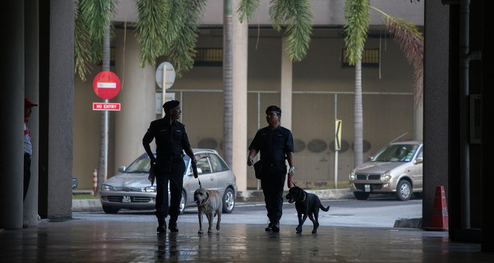 Dogs from the Malaysian Police K-9 unit join officers on patrol.