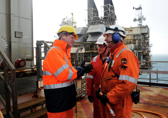 British Prime Minister David Cameron (L) talks with employees at the BP ETAP (Eastern Area Trough Project) oil platform in the North Sea, around 100 miles east of Aberdeen, Scotland on February 24, 2014