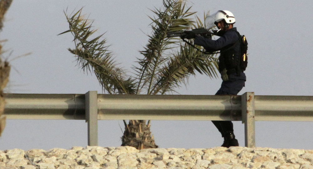 A riot policeman takes aim from a highway overpass at Bahraini anti-government protesters below