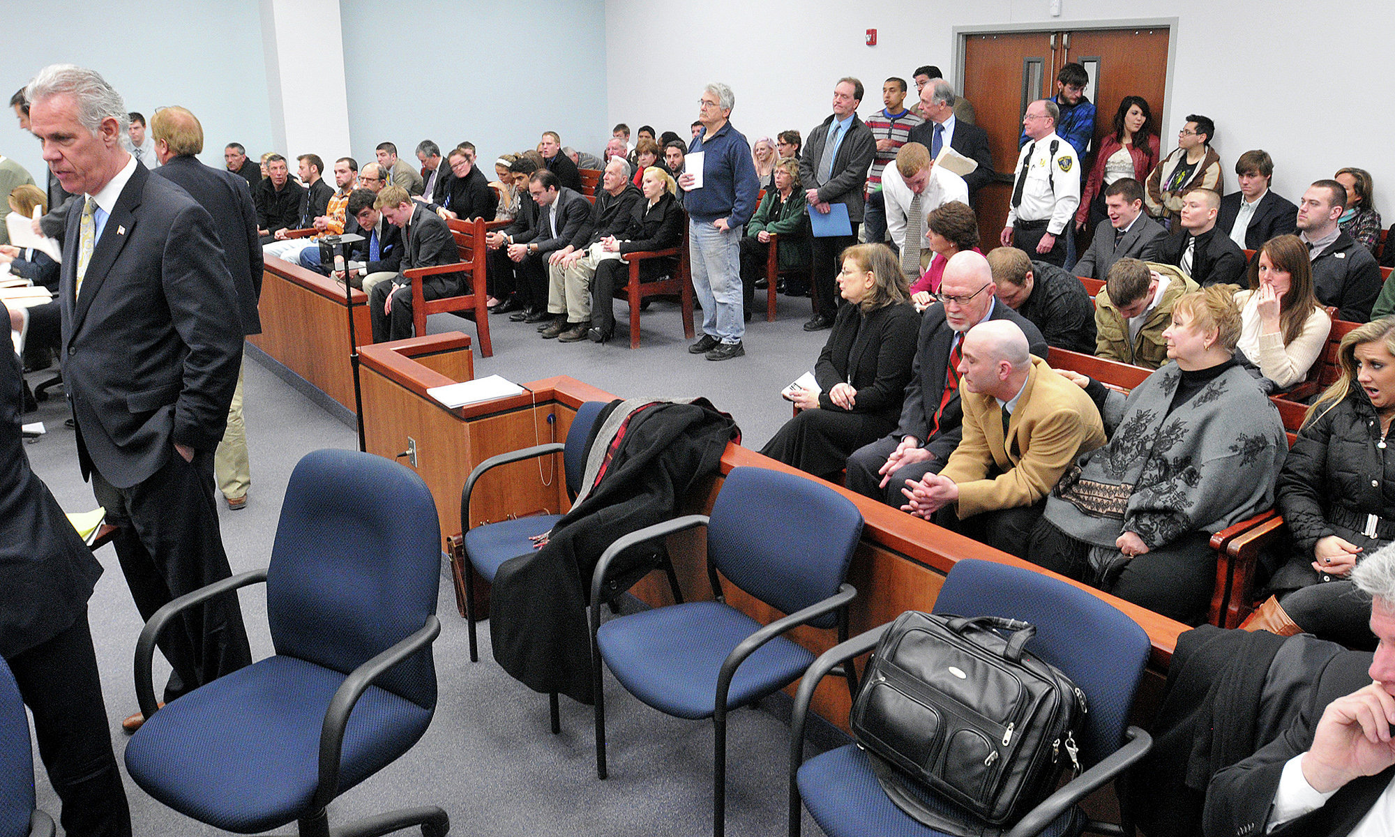People wait in a crowded courtroom at the Eastern Hampshire District Court in Belchertown, Mass., Monday, March 10, 2014 for individual arraignments of students arrested at a pre-St. Patrick's Day celebration at the University of Massachusetts, Amherst.