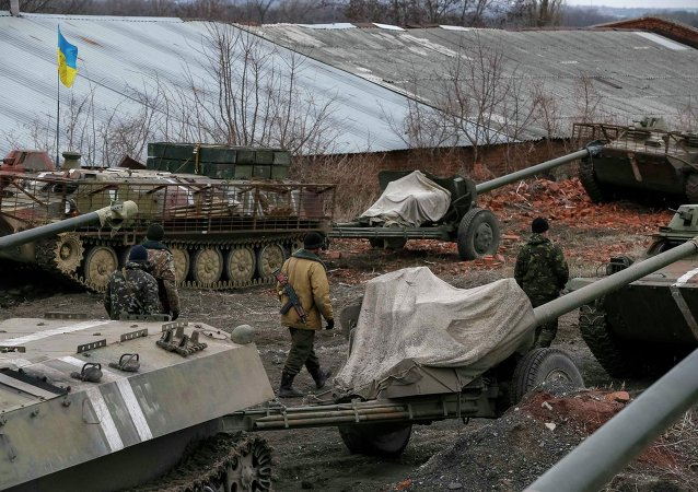 Ukrainian servicemen walk past armoured personnel carriers, military vehicles and cannons at their new position as they pull back from the Horlivka region, near Druzhkivka, eastern Ukraine