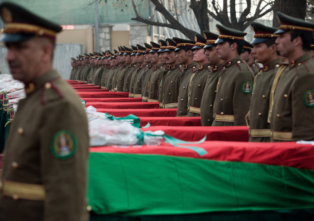 Afghan guards of honor stand next to the 21 coffins of Afghan national army soldiers during a ceremony at a military hospital in Kabul on February 24, 2014
