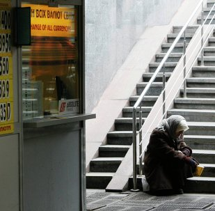 A woman sits next a currency exchange office in Kiev February 26, 2015