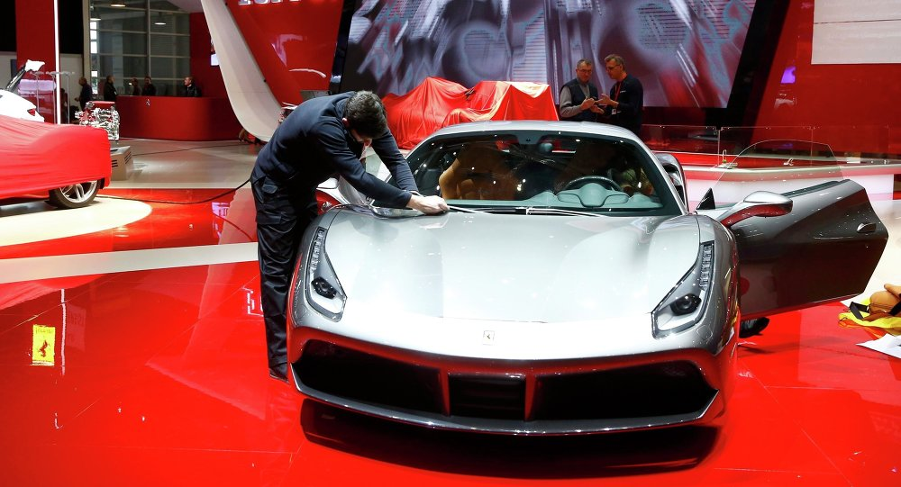An employee cleans a Ferrari car ahead of the 85th International Motor Show in Geneva, March 2, 2015