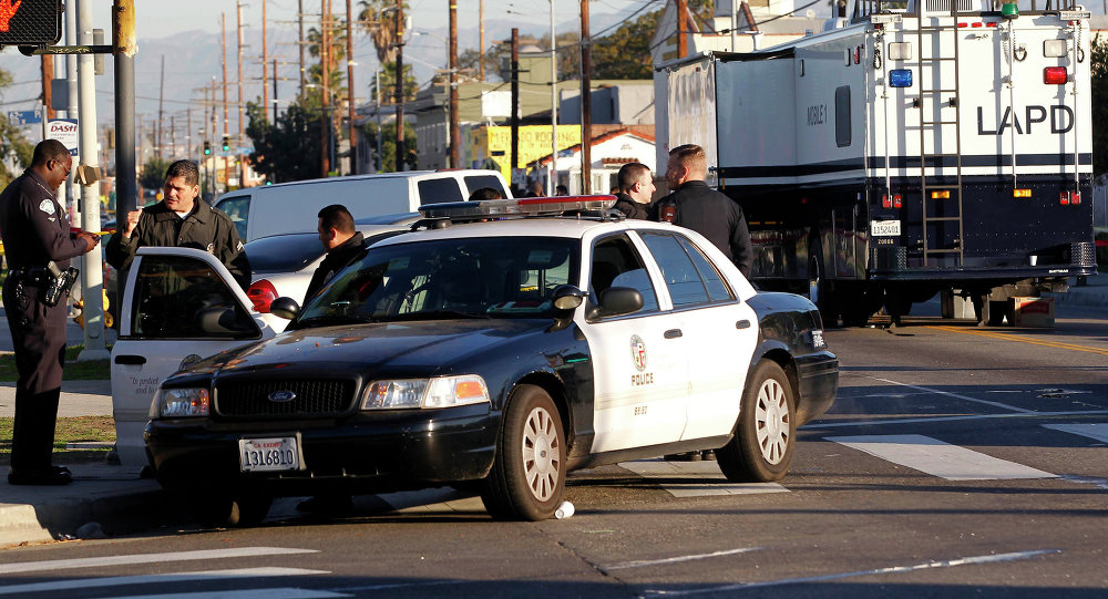 Los Angeles police officers investigate a shooting in South Central Los Angles on Monday, Dec. 29, 2014
