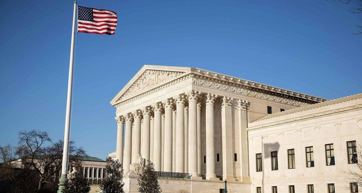The U.S. flag flutters near the Supreme Court in Washington March 2, 2015. The Supreme Court will hear King v. Burwell