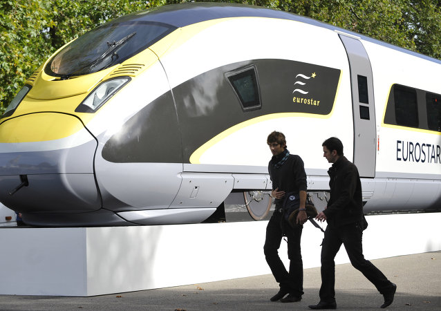 Pedestrians walk by a mock up of an Eurostar 320 high speed train in central London