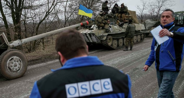 Members of Special Monitoring Mission of the Organization for Security and Cooperation (OSCE) to Ukraine walk along a convoy of Ukrainian armed forces in Paraskoviyvka, eastern Ukraine, February 26, 2015