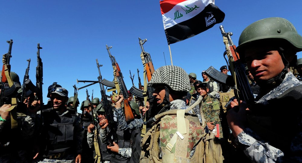 Members of the Iraqi security forces chant slogans in Al Hadidiya, south of Tikrit, en route to the Islamic State-controlled al-Alam town, where they are preparing to launch an offensive on Saturday, March 6, 2015