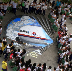 Students watch a three-dimensional graffiti as a way of sympathizing to the missing Malaysian Airlines flight MH370 at a school in Makati City, the Philippines
