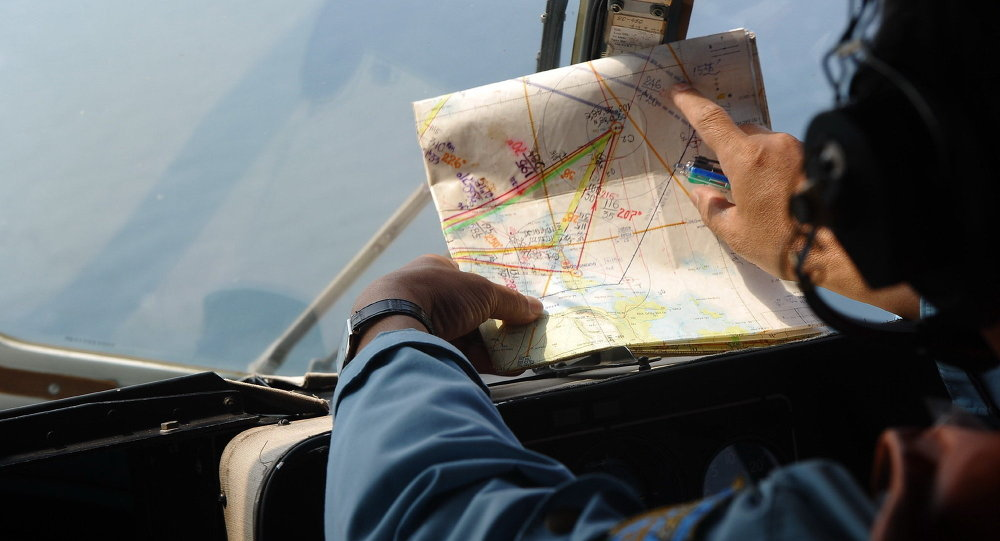 crew member checking a map during a search flight some 200 km over the southern Vietnamese waters off Vietnam's island Phu Quoc on March 11, 2014 as part of continued efforts aimed at finding traces of the missing Malaysia Airlines MH370