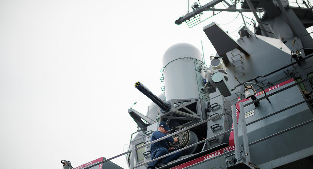 A sailor conducts maintenance on the Phalanx CIWS close-in weapon system aboard the Arleigh Burke-class guided missile destroyer USS Stout at Naval Station Norfolk in Norfolk, Virginia