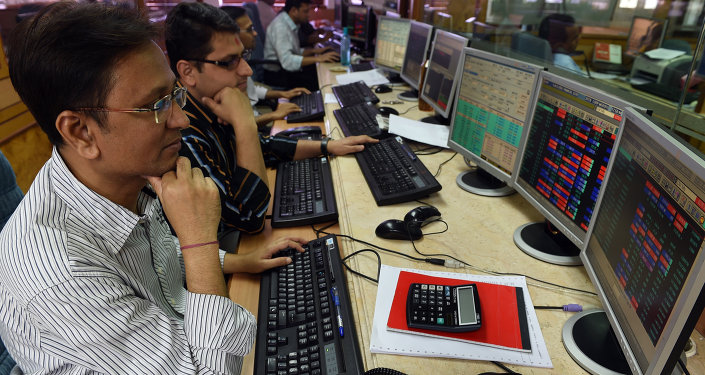 Indian stock dealers watch stock prices on their screen during intra-day trade at a brokerage house in Mumbai