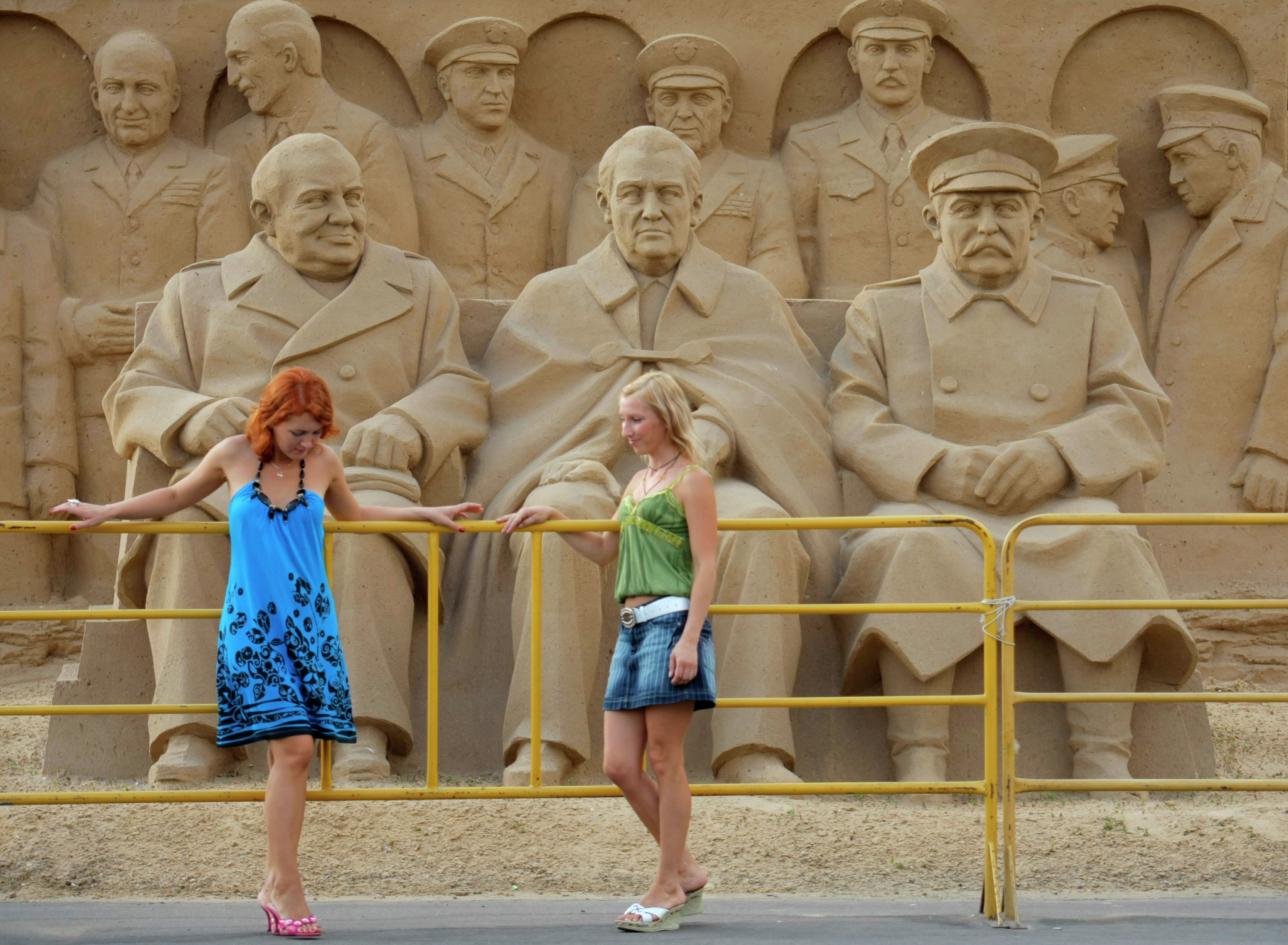 Girls stand in front of a sand sculpture