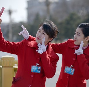 Chinese hostesses use a mobile phone to take a photo during the third session of the 12th National People's Congress outside the Great Hall of the People in Beijing