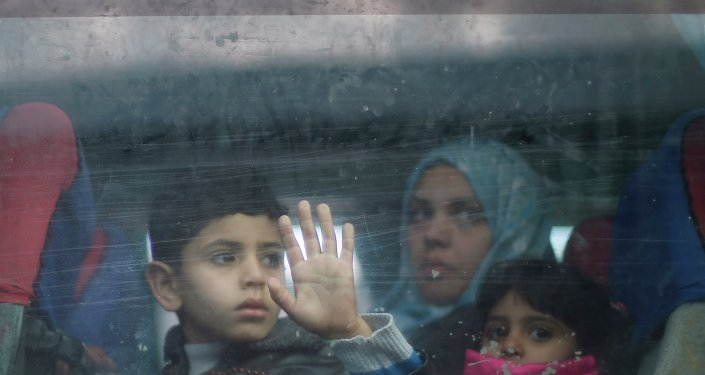 A Palestinian boy looks out a bus window as he waits with family to cross into Egypt, at the Rafah crossing between Egypt and the southern Gaza Strip