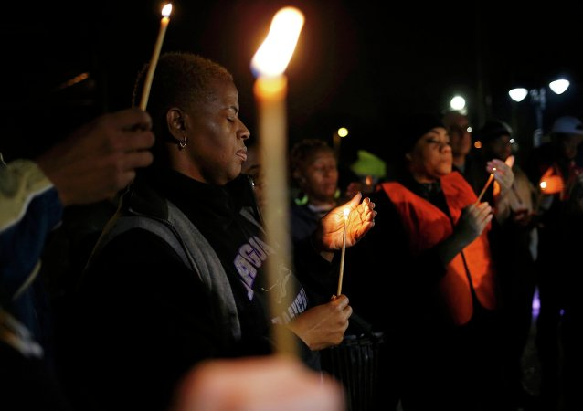 Protestors hold a candle-light vigil outside the Ferguson Police Department in Ferguson, Missouri, March 12, 2015
