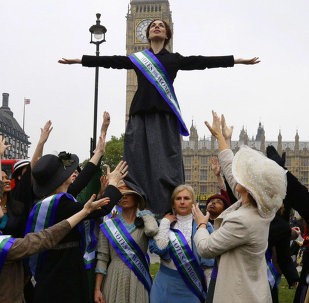 Women's rights activists from the UK Feminista organization, some dressed as suffragettes, stage a photo for the benefit of the media across the Houses of Parliament