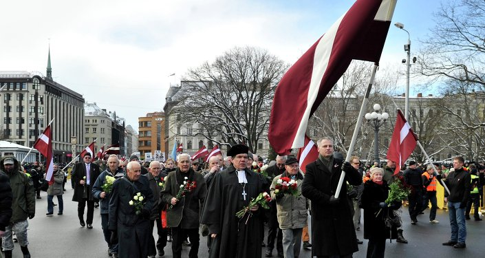 People carry Latvian flags as they march to the Freedom Monument to commemorate World War II veterans who fought in Waffen SS divisions, in Riga, Latvia, Sunday, March 16, 2014