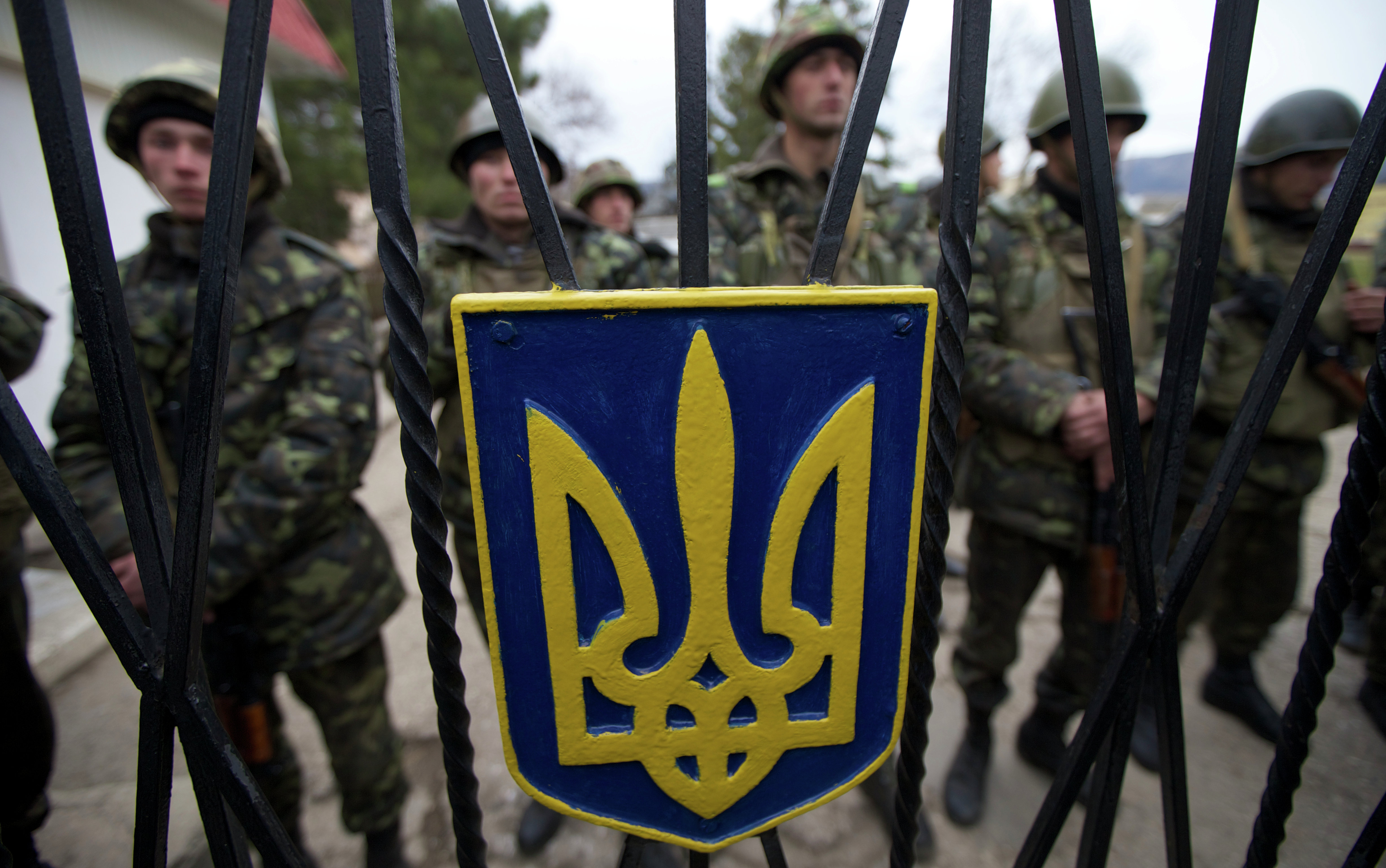 Ukrainian soldiers guard a gate to their military base in the village of Perevalne, outside of Simferopol, Ukraine, on Sunday, March 2, 2014