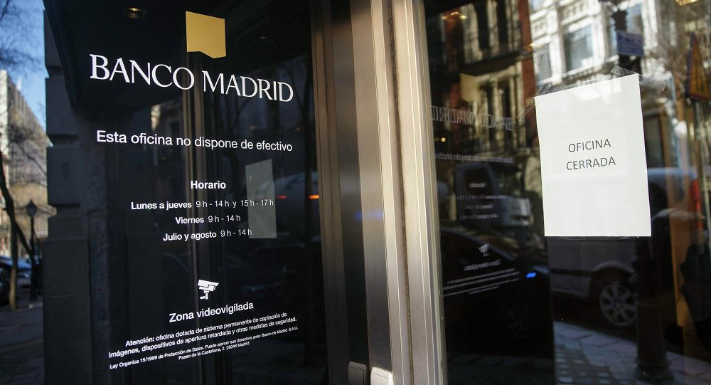 A sign taped to the door of a branch of Banco Madrid reads Office Closed, in Madrid