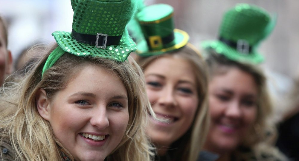 Three women take part in the St Patrick's Day parade through central London.