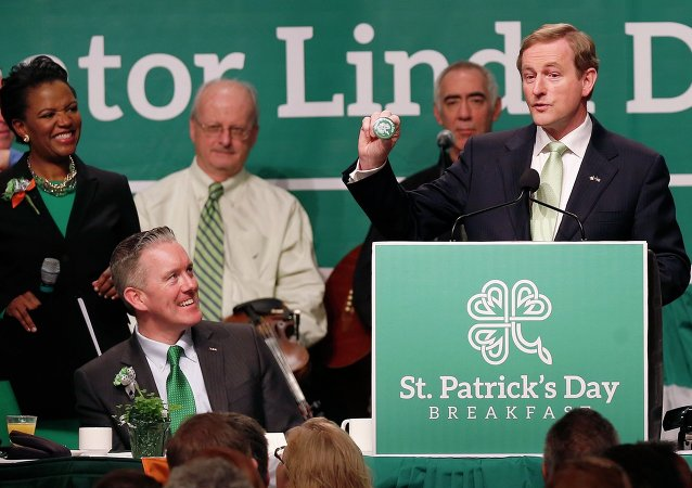 Prime Minister Enda Kenny of Ireland, right, holds a badge while speaking at the annual St. Patrick's Day Breakfast in Boston, as host state Sen. Linda Dorcena Forry, left, looks on, March 16, 2014.