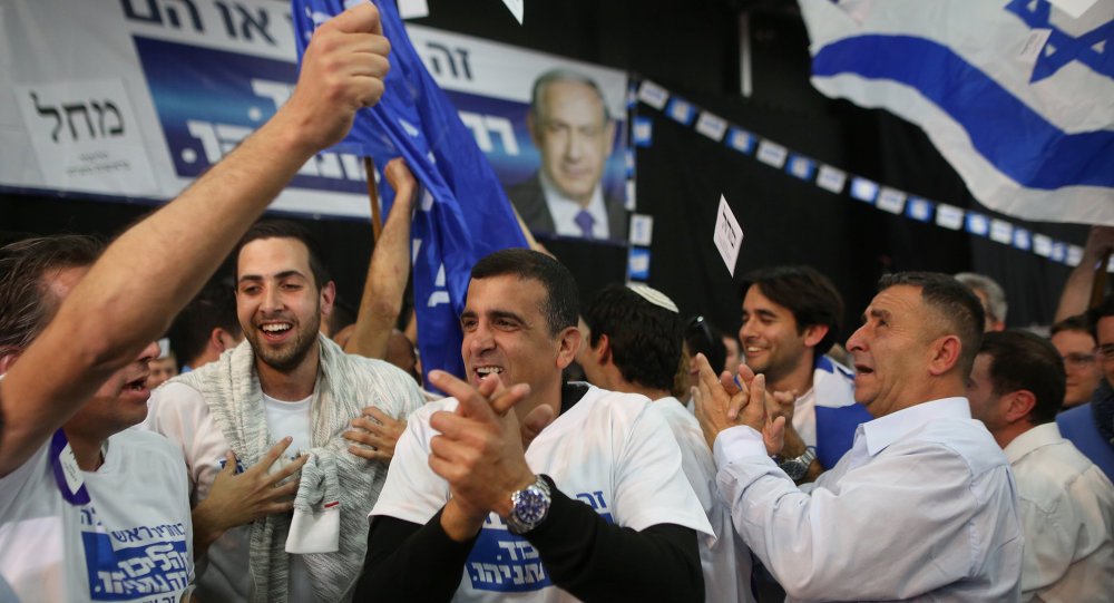 Israeli Likud Party supporters react to the exit polls while they wait for the announcement of the first official results of Israel's parliamentary elections on March 17, 2015 at the party's headquarters in the city of Tel Aviv