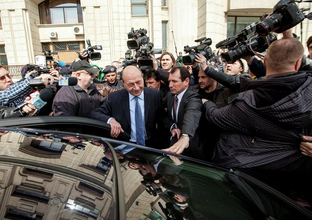 Former Romanian President Traian Basescu (C) is surrounded by the media as he leaves the Prosecutor General's office in Bucharest March 18, 2015