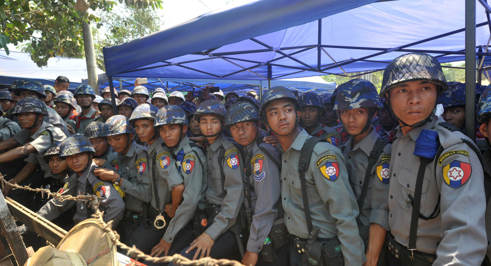 Myanmar riot police keep watch during a student protest march in Letpadan town, some 130 kilometres (80 miles) north of Myanmar's main city