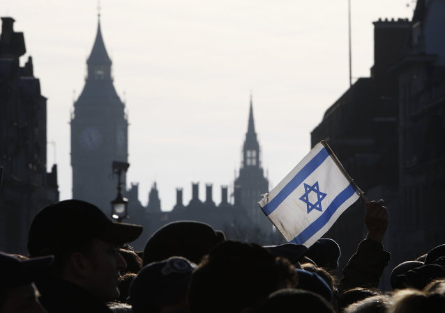 A demonstrator holds aloft an Israeli flag during a rally in Trafalgar Square in London