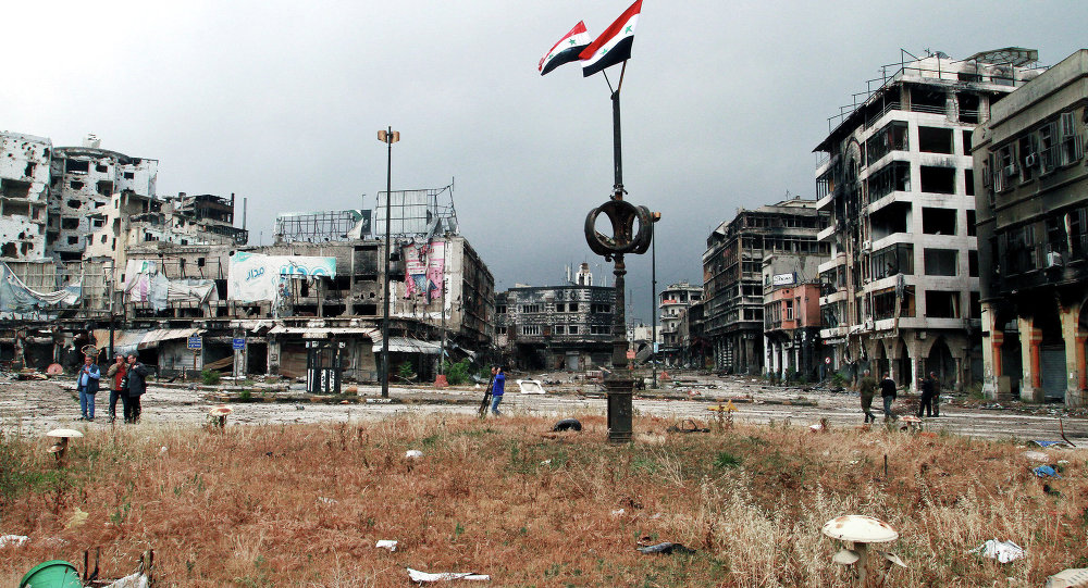 Two Syrian national flags hang on a pole as government officials inspect damages in the old city of Homs, Syria
