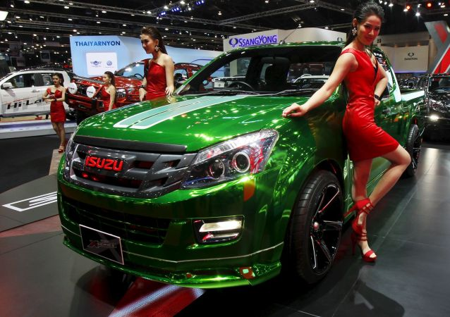 Models pose beside a Isuzu X-Series during a media presentation of the 36th Bangkok International Motor Show in Bangkok March 24, 2015