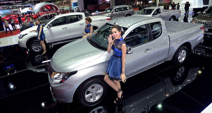 Models pose next to cars displayed at the 36th Bangkok International Motor Show on March 24, 2015