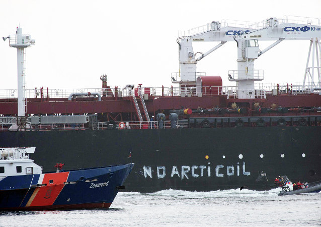 This image made available by environmental organization Greenpeace shows Greenpeace activists aboard an inflatable boat after painting 'No Arctic Oil' on the side of the Mikhail Ulyanov oil tanker in Rotterdam, Netherlands