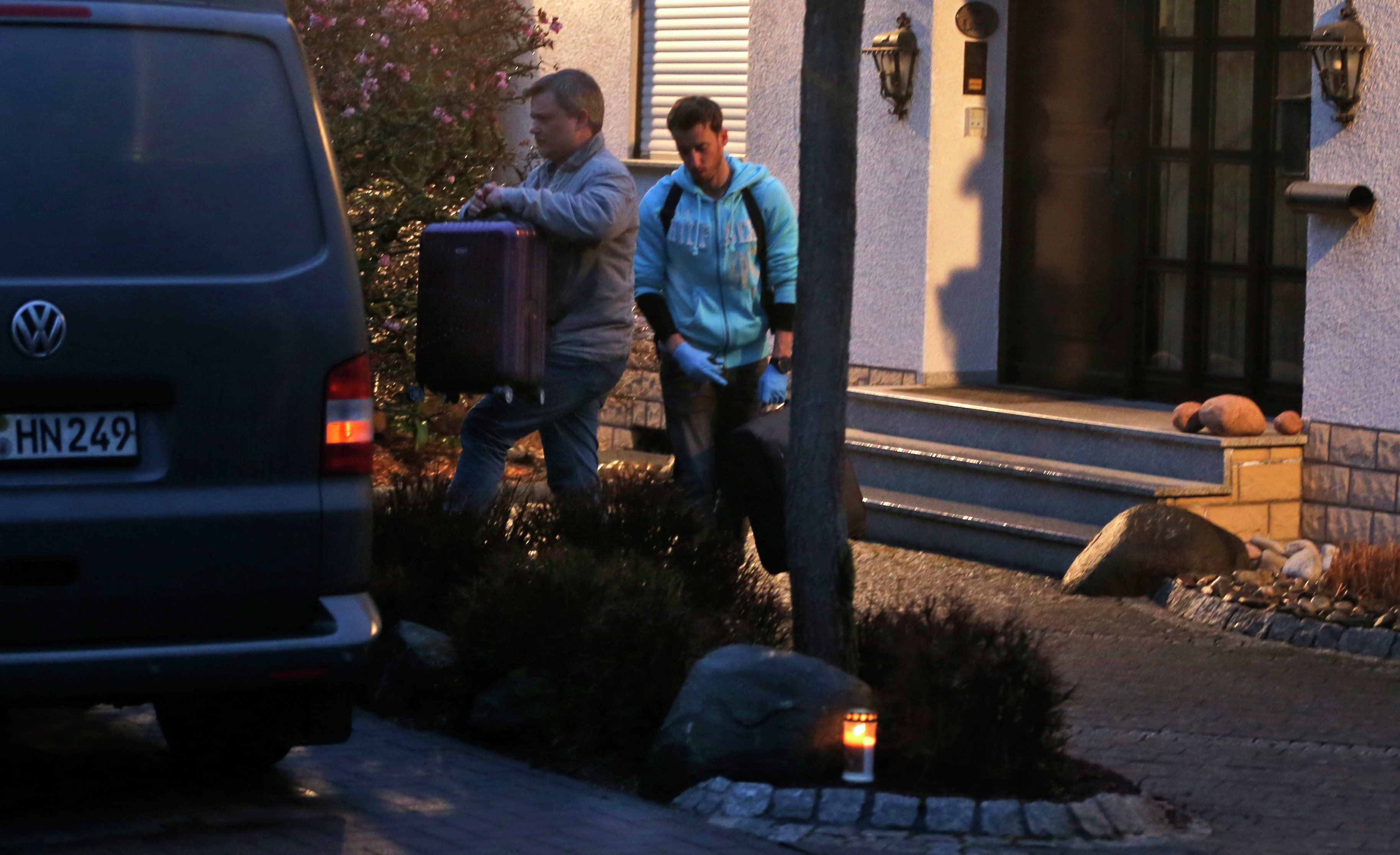 Investigators carry a suitcase out of the home of the family of Andreas Lubitz in Montabaur, Germany