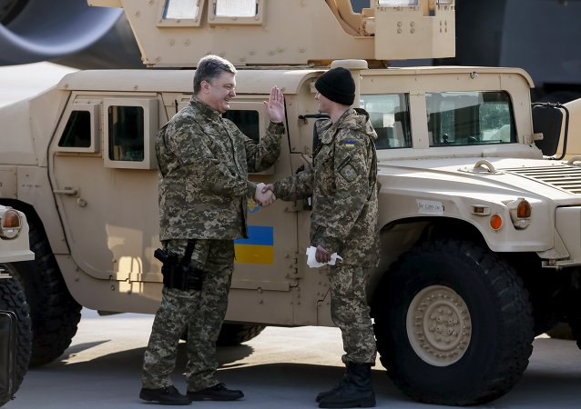 Ukraine's President Petro Poroshenko (L) welcomes a serviceman during a welcome ceremony for first plane from United State with non-lethal aid including ten Humvee vehicles to Ukraine at Borispol airport near Kiev, March 25, 2015
